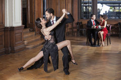 Tango Dancers Performing While Couple Dating In Restaurant. Confident tango dancers performing open legs step while couple dating in restaurant Stock Photography