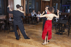 Tango Dancers Performing While Couple Dating In Restaurant. Full length of male and female tango dancers performing while couple dating in restaurant Stock Photo