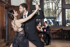 Tango Dancers Performing While Couple Dating In Restaurant. Mid adult tango dancers performing while couple dating in restaurant Royalty Free Stock Images