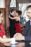 Tango Dancers Performing While Couple Sitting In Restaurant. Side view of young male and female tango dancers performing while couple sitting in foreground at Royalty Free Stock Photo