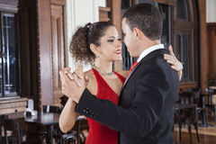 Tango Dancers Performing Gentle Embrace Step In Restaurant. Young male and female tango dancers performing gentle embrace step in restaurant Royalty Free Stock Photos