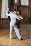 Tango Dancers Performing In Restaurant. Passionate male and female tango dancers performing in restaurant Stock Images