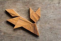 Tangram di legno come forma corrente del gatto su fondo di legno Fotografia Stock