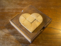 Tangram heart. Wooden game on a wooden table Stock Images