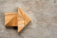 Tangram puzzle in arrow shape on wood background. Tangram puzzle in arrow shape on wooden background vector illustration