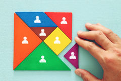 Tangram puzzle blocks with people icons ,human resources and management concept. Image of tangram puzzle blocks with people icons over wooden table ,human royalty free stock images
