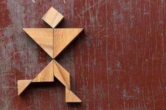 Tangram puzzle in joyful man run shape on red old wood background stock photo