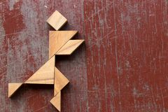 Tangram puzzle in joy man running shape on red old wood background stock photography