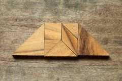 Tangram puzzle in trapezoid shape on wood background stock photos