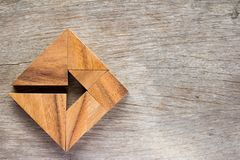 Tangrampussel som pil i fyrkantig form på wood bakgrund Co royaltyfri fotografi
