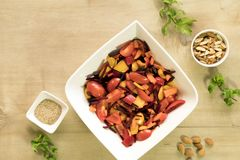 Tangy beetroot and bell pepper salad. Sliced tomato, beetroot and cubed bell pepper are mixed together with almonds, sesame seeds, lemon juice and rock salt Royalty Free Stock Photos