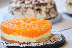 Tangy colourful citrus cheesecake. With a vivid orange topping over a creamy cheese filling displayed on a buffet table of assorted cakes for dessert Stock Photos