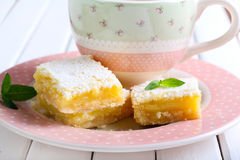 Tangy lemon squares. With icing sugar and cup of coffee stock photos