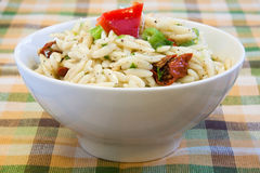 Tangy Rice Salad - Vegan. Vegan's delight. A tangy rice salad topped with red peppers, sun-dried tomatoes, spring onions and topped with dressing made with olive Stock Images
