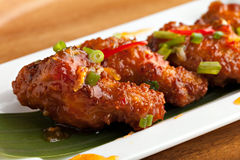 Tangy Thai Spicy Chicken Wings. Thai style spicy chicken wings appetizer on a contemporary white plate Royalty Free Stock Photo