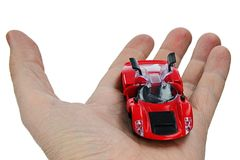 Tani czerwony klingerytu model legalnego rocznika bieżny samochód z rozpieczętowanymi gullwing drzwiami, trzymający w lewej palmi obraz royalty free