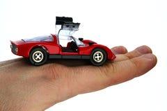 Tani czerwony klingerytu model legalnego rocznika bieżny samochód z rozpieczętowanymi gullwing drzwiami, trzymający wewnątrz na p fotografia stock