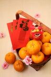 Tanjerinas na cesta com os pacotes vermelhos chineses do ano novo e a mini boneca do leão Fotografia de Stock Royalty Free