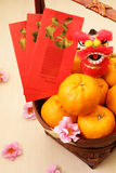 Tanjerinas na cesta com os pacotes vermelhos chineses do ano novo e a mini boneca do leão - série 6 Foto de Stock Royalty Free