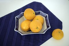 Tanjerinas no prato oriental na esteira azul Imagem de Stock