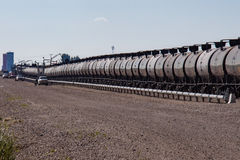 Tank Cars Being Loaded With Crude Oil. A line of railway tank cars being loaded with crude oil from a nearby shale oil field Royalty Free Stock Photography