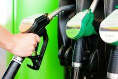 Tank de auto op een benzinestation bij Stock Foto's