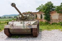 Tank in front of broken house. A photo of an old military tank M18 Hellcat parked in front of destroyed house. Photo taken at the Croatian Homeland War museum in Royalty Free Stock Photo