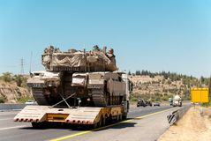 Tank Merkava carrier truck on the highway during the war in Israel Stock Photos