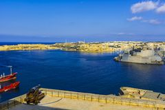 Cannon guarding port of Malta. Tank ship designed for transporting liquefied natural fuels in the port of Malta. Old cannon guarding the maltese fortress and Royalty Free Stock Image