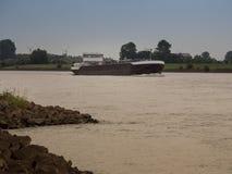 Tank ship drives upstream the rhine, Grieth am Rhein, Germany. On a very cloudy day Stock Photos