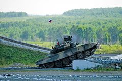 Tank T-80 shoots sideward. Shooting tank T-80 moving through cross-country terrain with obstacles Royalty Free Stock Image