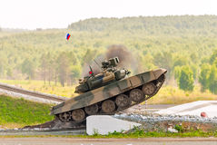 Tank T-80 overcomes a high concrete obstacle Stock Photography
