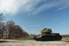 Tank T-34 standing by a road and trees Royalty Free Stock Images
