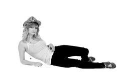 Tank Top Blonde. Blonde woman laying on her side in a hat, jeans and wife beater tank top royalty free stock images