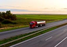 Tank transport of liquid, foodstuff. Metal chrome cistern tanker for food transportation on highway on sunset background
