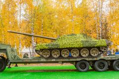 Tank under camouflage network on truck platform Stock Images