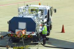 Tank vrachtwagen voor geparkeerd vliegtuig bij en wachtend tank het vliegtuig op grond in de luchthaven bij royalty-vrije stock afbeelding