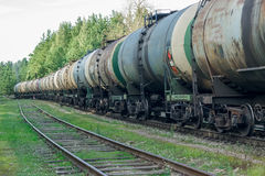 Tank wagons with oil. Freight train in forest stock photos