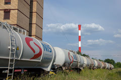 Tank wagons train from Nafta Industria Srbije passing near a factory chimney in an industrial district of capital city of Serbia Royalty Free Stock Image