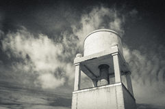 Tank of water. Tank or raised deposit of water in a tower whith clouds behind stock image