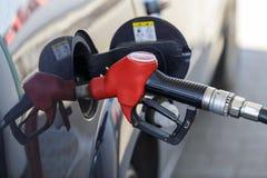 Tanka bilen på bensinstationen Arkivbild