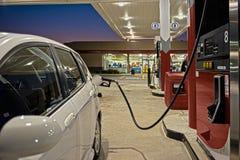 Tanka bilen på bensinstationservicebutiken Arkivbild