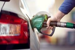 Tanka bilen på en bensinstationbränslepump arkivfoto