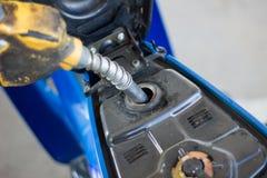 Tanka en motorcykel på en bensinstation i Thailand Fotografering för Bildbyråer