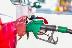 Tanka en röd bil på bensinstationen Fotografering för Bildbyråer
