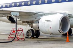 Tanka flygplan, sikt av vingen, slang, motor Flygplatsservice Royaltyfri Foto