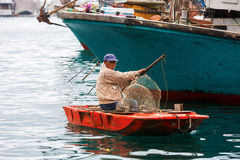 Tanka Man with a boat in the harbour of Aberdeen, Hong Kong Stock Image
