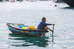 Tanka man in a canoe in the harbour of Aberdeen, Hong Kong Royalty Free Stock Image