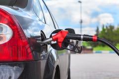 Tanka medlet med bensin på bensinstationen Arkivbild