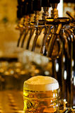 Tankard of beer with a frothy head. Close up view of tankard of beer with frothy white head standing on bar counter in pub with selective focus to  glass Royalty Free Stock Photos